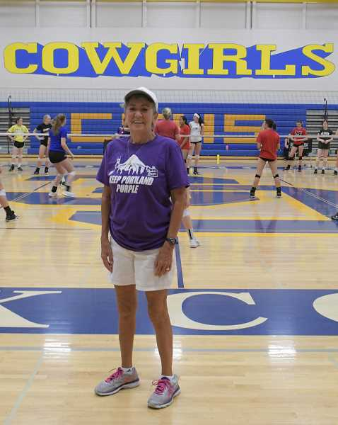 LON AUSTIN/CENTRAL OREGONIAN - Rosie Honl poses for a photo while volleyball teams practice in the background. Honl, the long-time Crook County High School head volleyball coach, recently retired from teaching and coaching. This team camp is scheduled to be her last.
