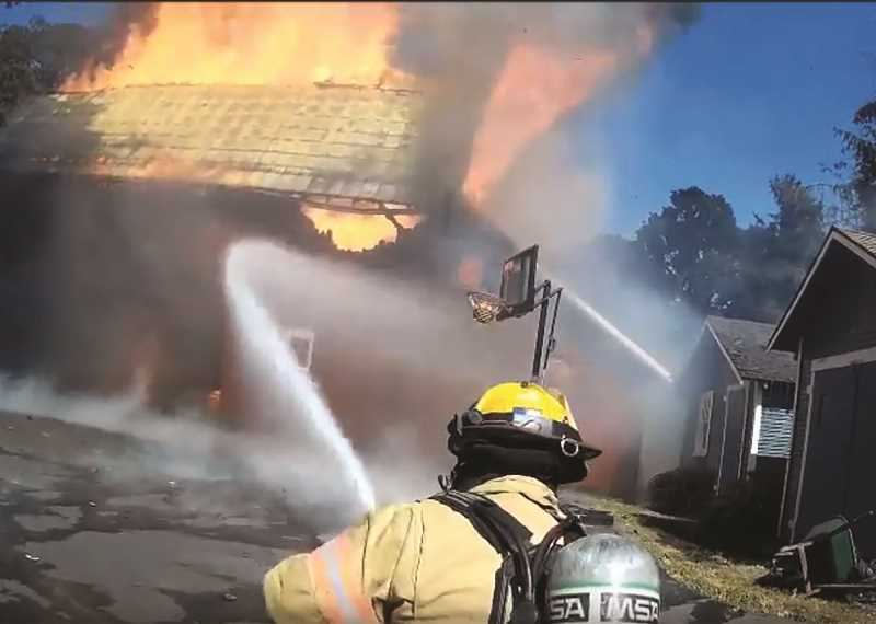 COURTESY PHOTO: WOODBURN FIRE DEPARTMENT - Woodburn Firefighter Mitchell Raines trains a nozzle on the flames during a fire which destroyed a historic barn at the Wooden Shoe Tulip Farm on Friday.