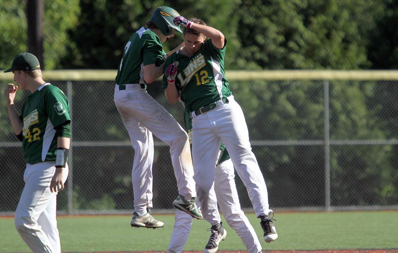 TIDINGS PHOTO: MILES VANCE - West Linn's Zach Bell (No. 12) and Cormac Duffy celebrate after Bell's walk-off hit beat Tualatin 7-6 in nine innings at Lake Oswego High School on Friday.