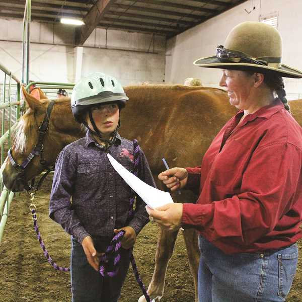 HOLLY SCHOLZ/CENTRAL OREGONIAN - Calvary Riders 4-H Club leader Kitty Lauman gives her daughter, 12-year-old Josie Lauman, some last-minute tips before she heads to the ground training class with her filly mustang, Samantha.