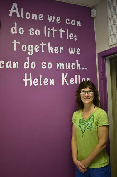 ESTACADA NEWS PHOTO: EMILY LINDSTRAND - Estacada Area Food Bank Director Debra Bufton stands in front of a repainted wall at the pantry, which now features a quote by Helen Keller. Many community members came together to help with the remodel project at the food bank.
