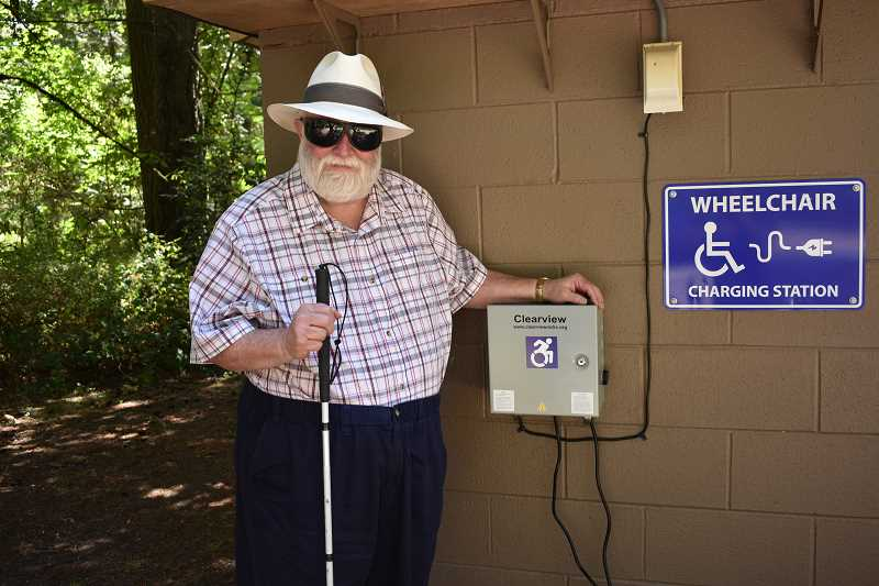 ESTACADA NEWS PHOTO: EMILY LINDSTRAND - Michael Foley stands next to the new wheelchair charging station at Barton Park. Foley, who volunteers with the Oregon Office on Disabilities and Health, was involved with the installation.