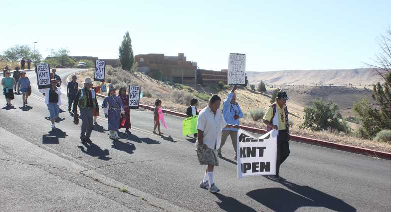 SUSAN MATHENY/MADRAS PIONEER - Warm Springs elders and supporters, including two tourists, marched from the resort's lodge to the village and swimming pool area carrying signs protesting the closure of Kah-Nee-Ta, on Saturday.
