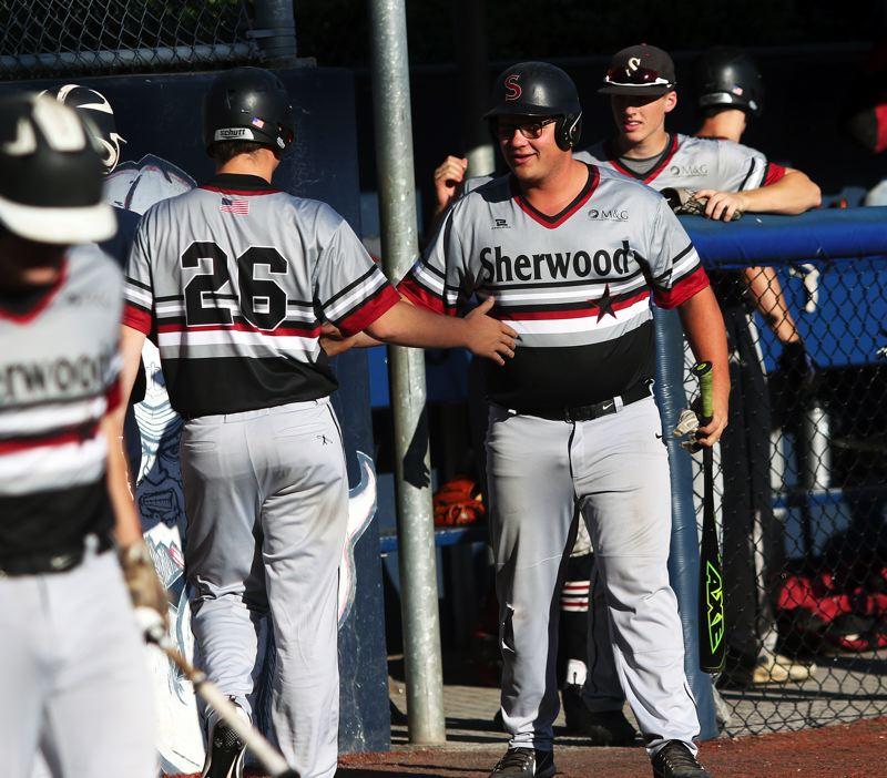 TIMES PHOTO: DAN BROOD - Sherwoods Nick Severson (right) congratulates Kaden Emmons after he scored a second-inning run in the OIBA playoff game with Grant.