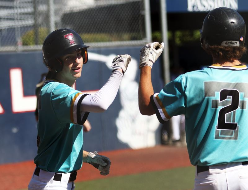 TIMES PHOTO: DAN BROOD - Tualatins Joey Myers (left) is congratulated by Cameron Atkinson after scoring a fifth-inning run during the teams tourney game with West Linn.