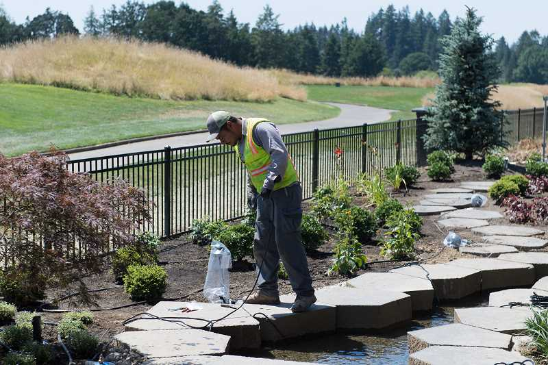 STAFF PHOTO: CHRISTOPHER OERTELL - Landscapers install irrigation lines in the backyard of a home at the Street of Dreams in Hillsboro, on July 17.