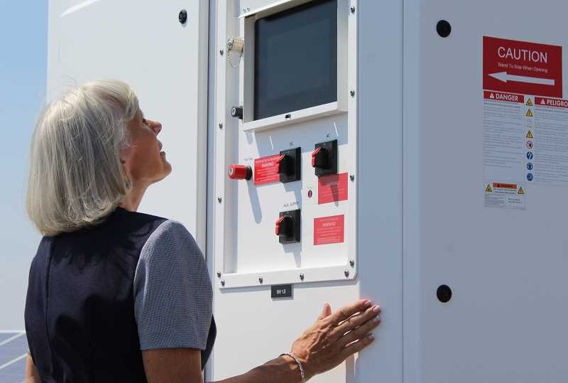 HOLLY M. GILL - Jefferson County Commissioner Mae Huston examines an inverter on the project. The project's five inverters convert he electrical current from the panels into electricity that is sent through nearby wires to the substation. The panel on the inverter also lets operators monitor the solar array's production.