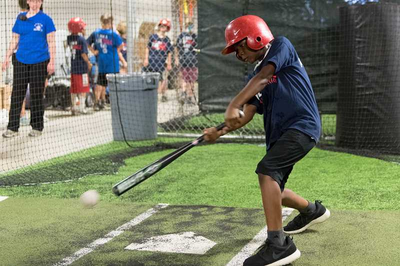 STAFF PHOTO: CHRISTOPHER OERTELL - Ajani Perry, 9, connect with a ball in the Hillsboro Hops batting cage on July 23. Perry is one of more than 100 kids to take part in a one-day event at Ron Ronkin Field.