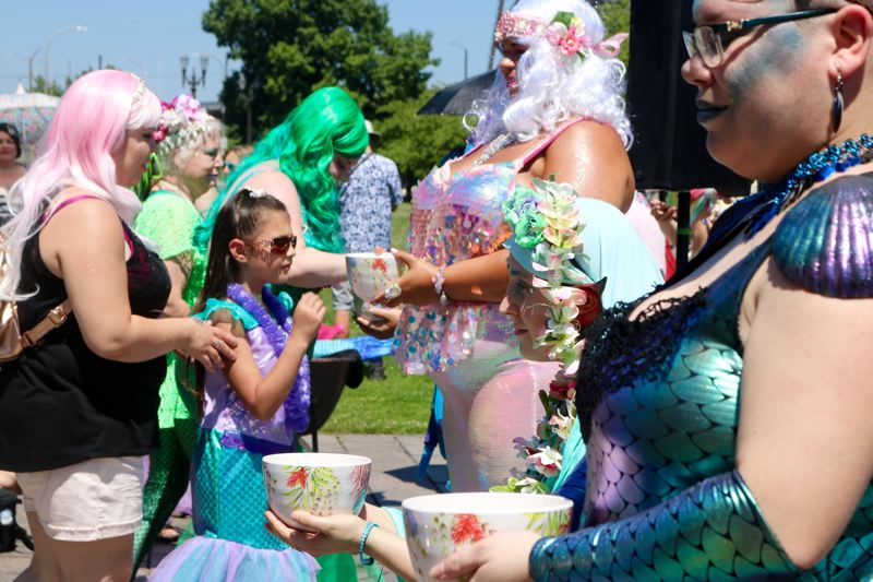 TRIBUNE PHOTO: ZANE SPARLING - People take seashells from bowls during the opening invocation of the Portlandia Mermaid Parade on Saturday, July 28 in downtown Portland.