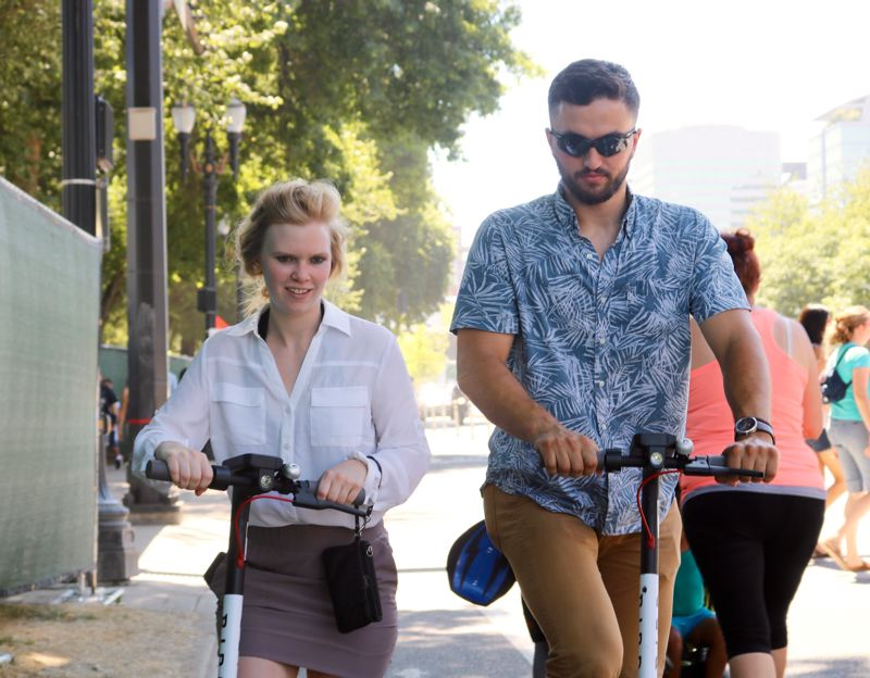TRIBUNE PHOTO: ZANE SPARLING - Sam Kane and Caitlin Drost say Bird brand electric scooters are 'super fun' and 'pretty awesome,' respectively.