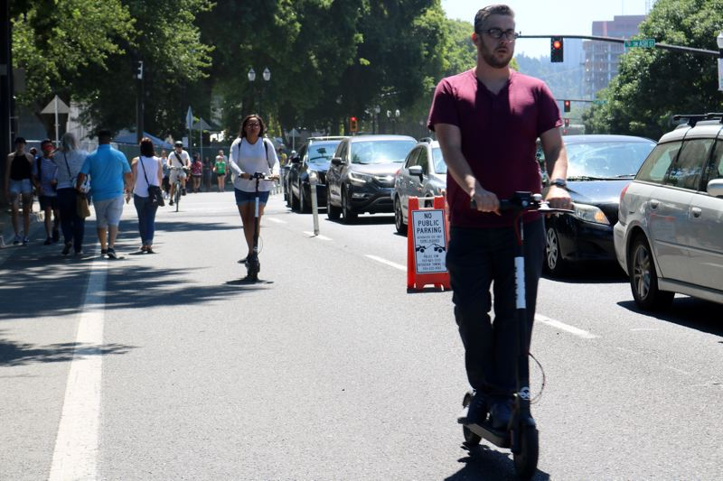 TRIBUNE PHOTO: ZANE SPARLING - Two people ride electric scooters on the Better Naito section of Southwest Naito Parkway on Saturday, July 28 in downtown Portland.