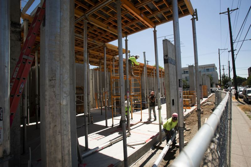 PORTLAND TRIBUNE: JAIME VALDEZ - Construction crews working on an apartment buildings along Southeast Grand Avenue, just one of many projects competing for workers and city regulators.