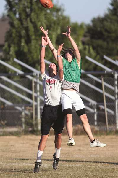 PHIL HAWKINS - North Marion junior Joe Torian rises up to intercept a pass targeted to a Santiam reciever in the Huskies' 7-on-7 practice at Woodburn High School on July 17.