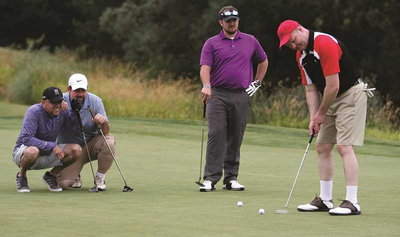 PHIL HAWKINS - Luis Molina and Brock Rempel huddle to the side, while Shawn Moyer-DeMarre stands to watch teammate Lucas Villa attempt a put on the ninth green at the OGA Golf Course in Woodburn on July 19.