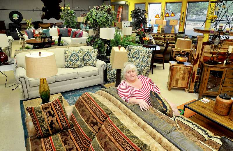 GARY ALLEN - Vineyard Valley Furniture owner Terie Thomas sits amid the stock available for purchase at the Elliott Road store.