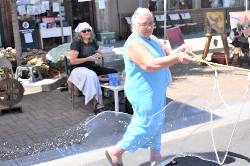 ESTACADA NEWS PHOTO: EMILY LINDSTRAND - Spiral Gallery Artist Annette Reisbick creates giant bubbles while fellow artist Brenda Scott admires as she throws pottery at the Estacada Summer Celebration.