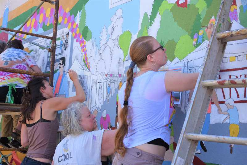 ESTACADA NEWS PHOTO: EMILY LINDSTRAND - Estacada Artback members paint their 2018 mural project, Celebration of Summer, which is located on the Dollar General building at 416 Broadway St.