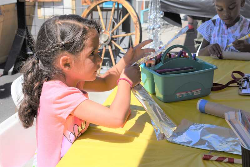 ESTACADA NEWS PHOTO: EMILY LINDSTRAND - A young artist at Summer Celebration focuses as she creates a new project.