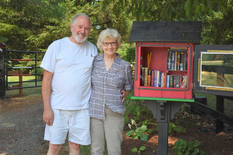 ESTACADA NEWS PHOTO: EMILY LINDSTRAND - Jerry and Martha Galarneau smile in front of their Little Free Library at  22012 S.E. Howlett Road.