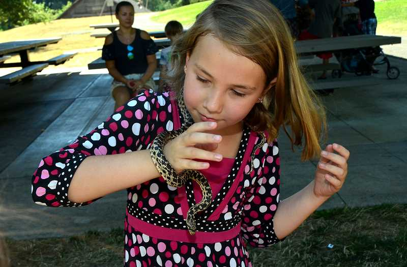 Ayla Reed of Wilsonville makes friends with one of the snakes.
