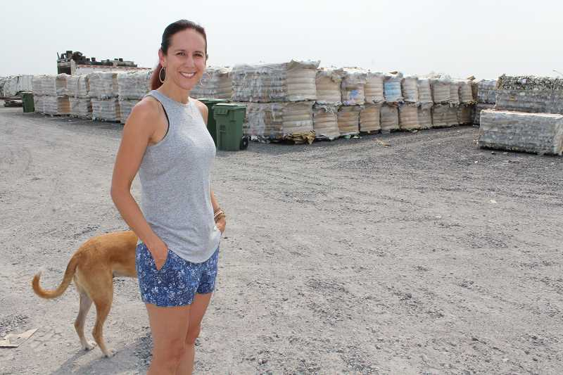 HOLLY M. GILL/MADRAS PIONEER - Melanie Widmer, of Madras Sanitary Service, and dog, Rossi, stand in front of the 200 tons of baled materials that are ready for recycling, with no place to go.