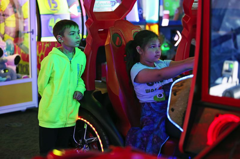 TIMES PHOTO: JESSIE DARLAND - Kids race through city streets in an arcade game at the new KingPins Family Entertainment Center.