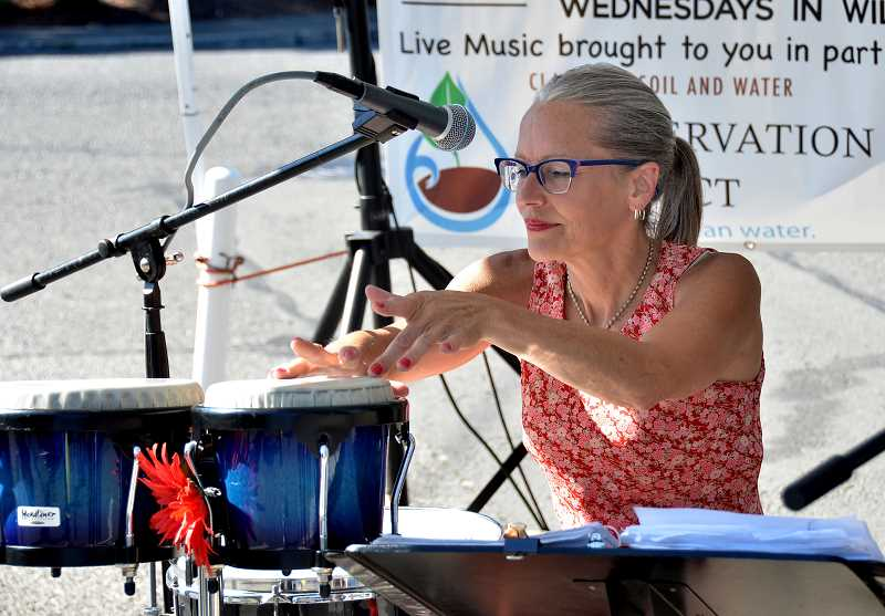 TIDINGS PHOTO: VERN UYETAKE - Beth Rodes Moffett of Crows Feet plays percussion. Market Manager Eric TwoRivers hopes music and other attractions will continue to prompt more residents to stop by the market