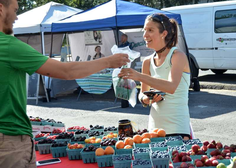 Emily Axelrod purchases some fresh berries from a vendor.