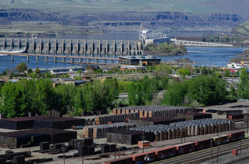 PHOTO BY SARAH CLARK, COURTESY OF CASCADIA TIMES - Railroad cross-ties treated with creosote are stored at the AmeriTies West plant in The Dalles as the Columbia River spills over The Dalles Dam.