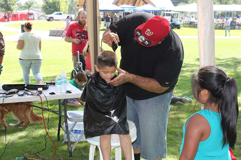 JENNIFFER GRANT/MADRAS PIONEER - Volunteer William Walker cuts Adrian Felix's hair at the 2017 Our Community event at Sahalee Park. This year's event will be held from 9 a.m. to 4 p.m. at Sahalee Park, with a wide variety of free services, activities and food.