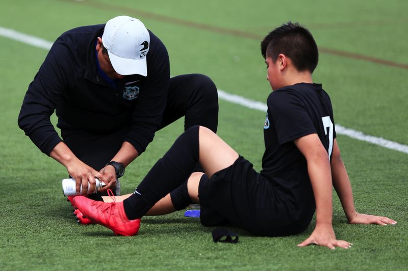 PAMPLIN MEDIA GROUP PHOTO: JESSIE DARLAND - Cuervos club president José Alberto Vasquez, shown here attending to his son, Edison, says his coaches take injuries, including concussions, very seriously.