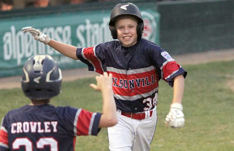 PAMPLIN MEDIA GROUP FILE PHOTO: MILES VANCE - Wilsonvilles Justin Schramm smiles after scoring late in his teams 11-5 win over Lake Oswego in the District 4 Majors tournament at Alpenrose Dairy Stadium July 9.