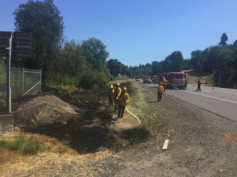 PHOTO COURTESY OF SCAPPOOSE FIRE DISTRICT - Scapppoose Fire District crews and other emergency officials respond to a brush fire along Highway 30, north of Cornelius Pass Road on July 29. County agencies have responded to numerous brush fires during a stretch of dry, hot weather in the region.