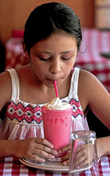 PAMPLIN MEDIA GROUP: VERN UYETAKE  - Sophia Pompello, 10, sips on an Italian soda on Tuesday, July 31, at her familys business, Ristorante di Pompello, where plastic straws still automatically come with sodas. The eatery will switch to paper sippers if straw bans are enacted in East Multnomah County.