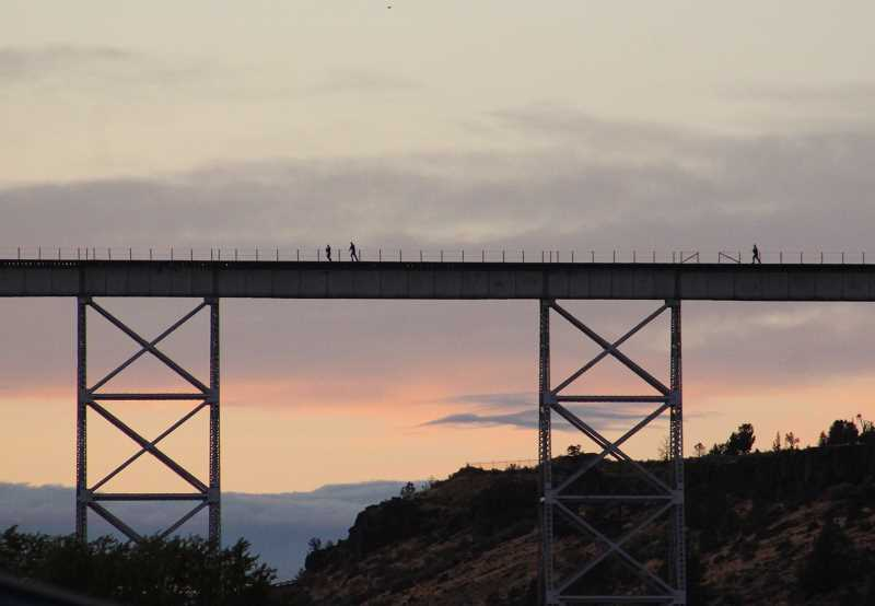 HOLLY M. GILL/MADRAS PIONEER - A photograph of law enforcement officers chasing a suspect across the train trestle, taken by Madras Pioneer Managing Editor Holly Gill, won first place in the Oregon Newspaper Publishers Association 2018 Best Newspaper Contest in the category of Best News Photo.