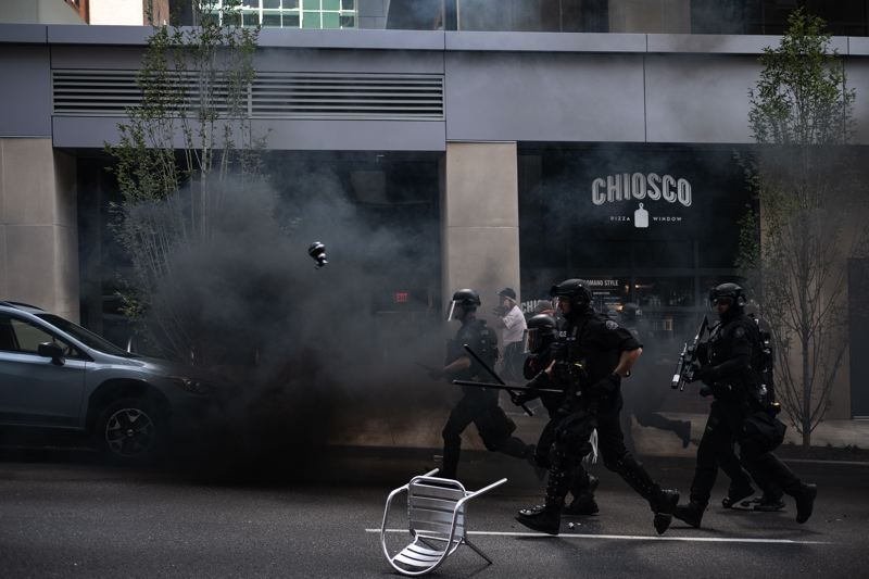 COURTESY PHOTO: CLINT KAMSTRA - Portland police in riot gear throw flash-bang grenades and head toward groups gathered on Southwest Second Avenue during a massive protest Aug. 4 in downtown Portland.