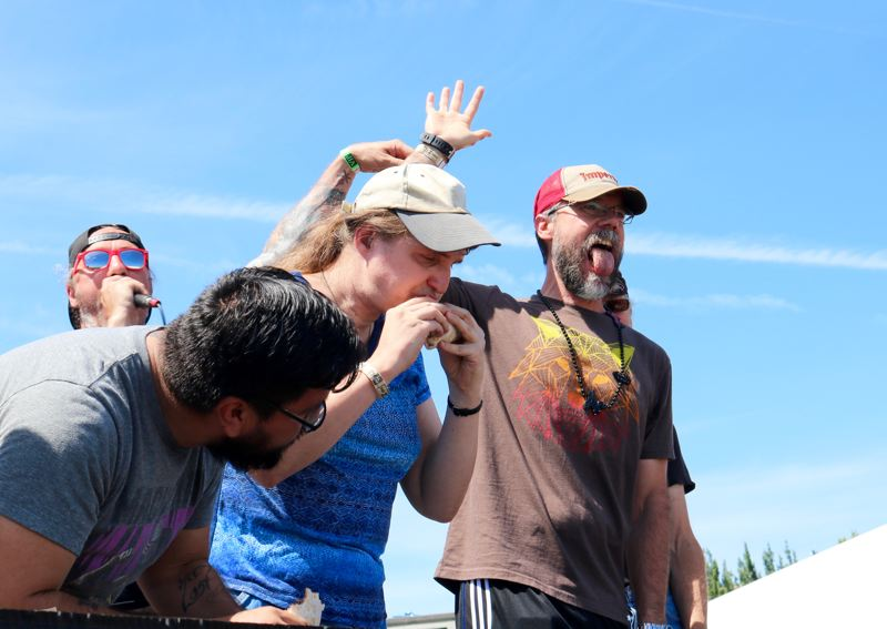 TRIBUNE PHOTO: ZANE SPARLING - Bill Frost of Denver, Colorado displays his empty mouth after besting nine others during a eating contest featuring 'Slaytanic' burritos stuffed with Reaper peppers at the PDX Hot Sauce Expo on Sunday, Aug. 5.
