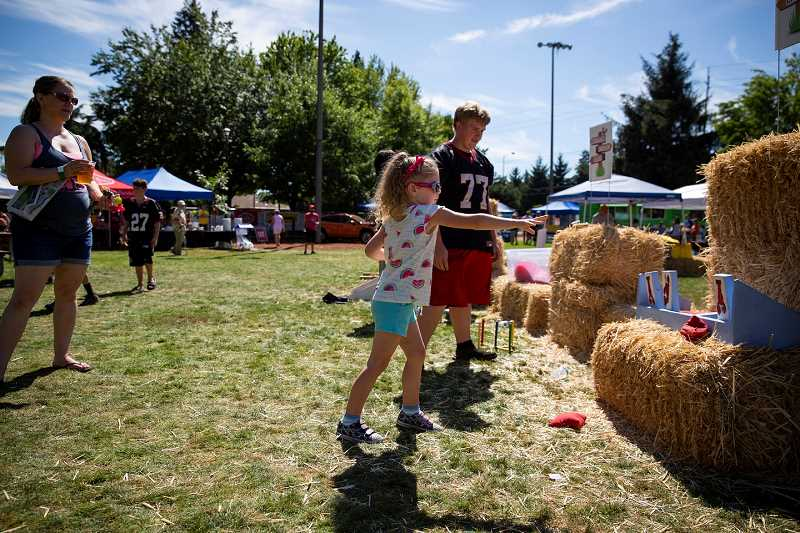 PAMPLIN MEDIA GROUP: ADAM WICKHAM - Lucy Drake, 5, plays a crawfish-themed toss game at the Tualatin Crawfish Festival held Saturday at Tualatin Community Park.