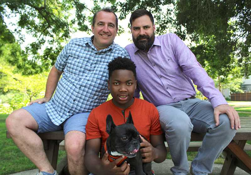 SPOKESMAN PHOTO: SAM STITES - The Rummell-West family poses for a photo in a park near their Villebois home in Wilsonville. From left: Paul Rummell, JayQuan Rummell-West (with Olive the dog) and Ben West.