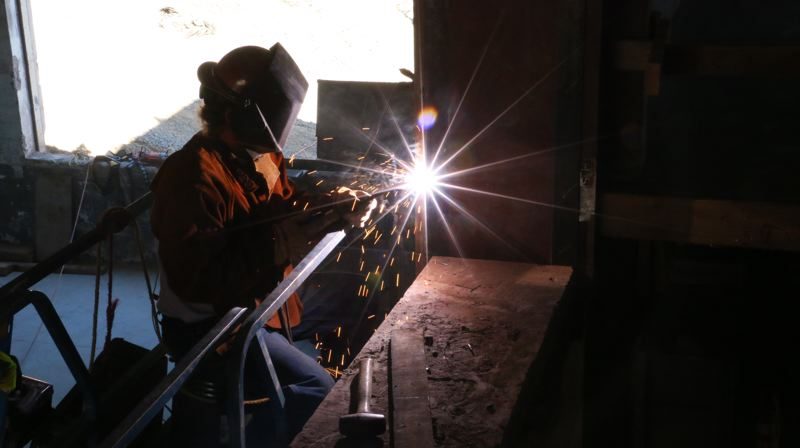COURTESY: PORTLAND PUBLIC SCHOOLS - A construction worker at Grant High School welds as part of the remodel.