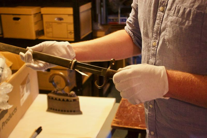 OUTLOOK PHOTO: CHRISTOPHER KEIZUR - Matt Holland examines a bayonet in the basement of the Gresham History Museum.