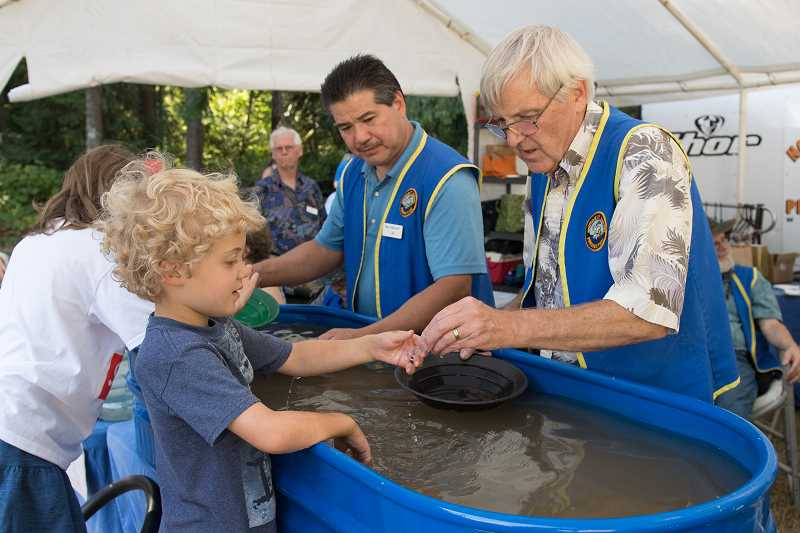 STAFF PHOTO: CHRISTOPHER OERTELL - Soren McKinney, 5, of Portland, pans for gold with the help of NW Prospectors Club member Bill Krause during the Rice Northwest Museum of Rocks and Minerals Summer Fest on Sunday, Aug. 5.