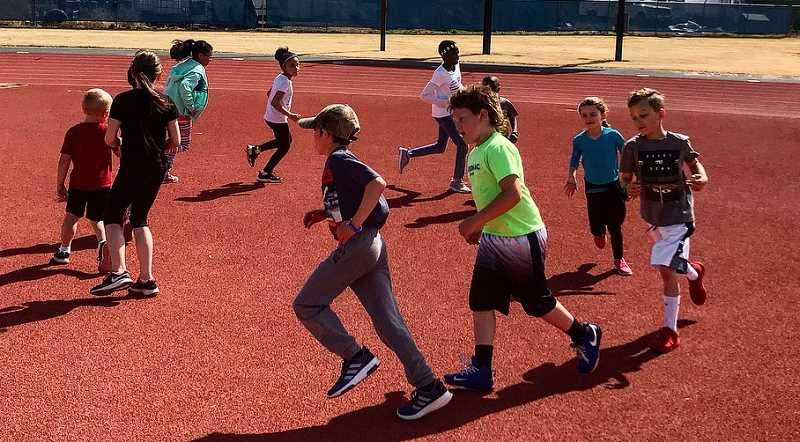 SUBMITTED PHOTO - MHS youth camp participants warm up before they run. The camp was during spring break.