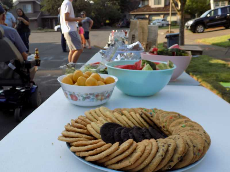 TIMES PHOTO: RAY PITZ - Neighbors all pitched in to donate to long tables of potluck fare during Tuesday nights observation of National Night Out.