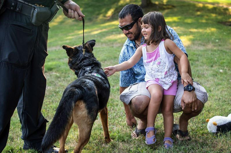 TIMES PHOTO: JONATHAN HOUSE - Gabriella Cintron and her father Marcos meet Tony, a police dog with Tualatin Police Department, during a National Night Out event at Lafky Park in Tualatin.