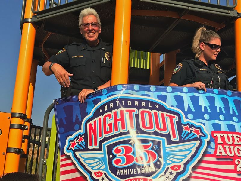 TIMES PHOTO: DANA HAYNES - Tigard Police Chief Kathy McAlpine, left, and Officer Kaci Mace tie a National Night Out banner to a play structure in the River Terrace neighborhood.