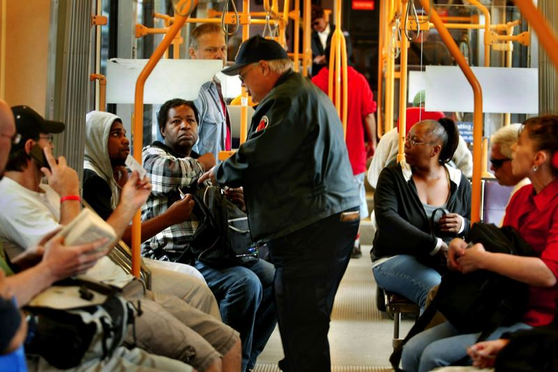 PORTLAND TRIBUNE FILE PHOTO - A TriMet fare inspector checks a passenger's fare on a MAX train.