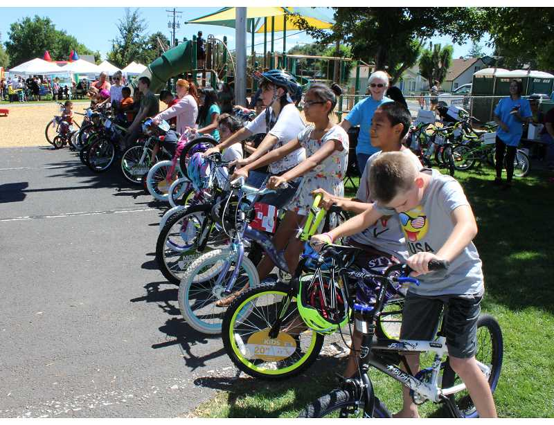 HOLLY M. GILL/MADRAS PIONEER - Fifty-five kids received new bikes at the Our Community event Saturday at Sahalee Park.