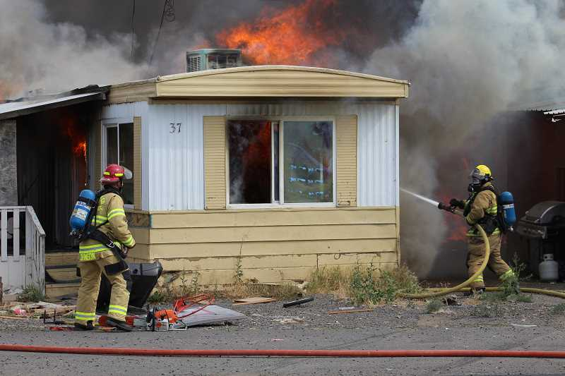 HOLLY GILL/MADRAS PIONEER - Firefighters hose down flames that spread from unit 39, at right, to unit 37 on July 31, at Tops Trailer Park.