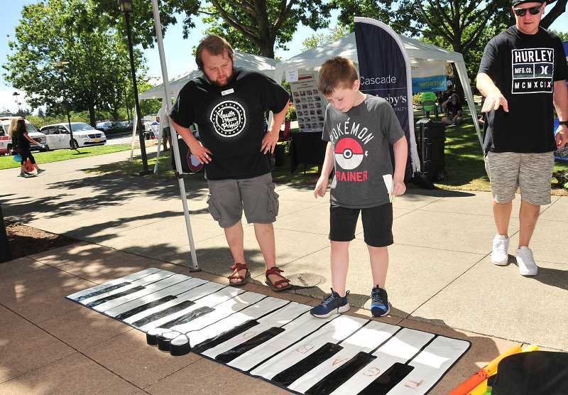 SPOKESMAN PHOTO: VERN UYETAKE - Carter Johnston, right, learns to play a tune with help from Peter McCoid of the Youth Music Project.